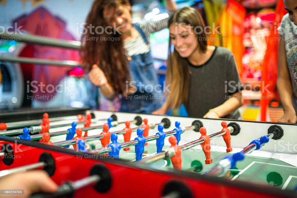 friends playing foosball at the arcade game stock photo
