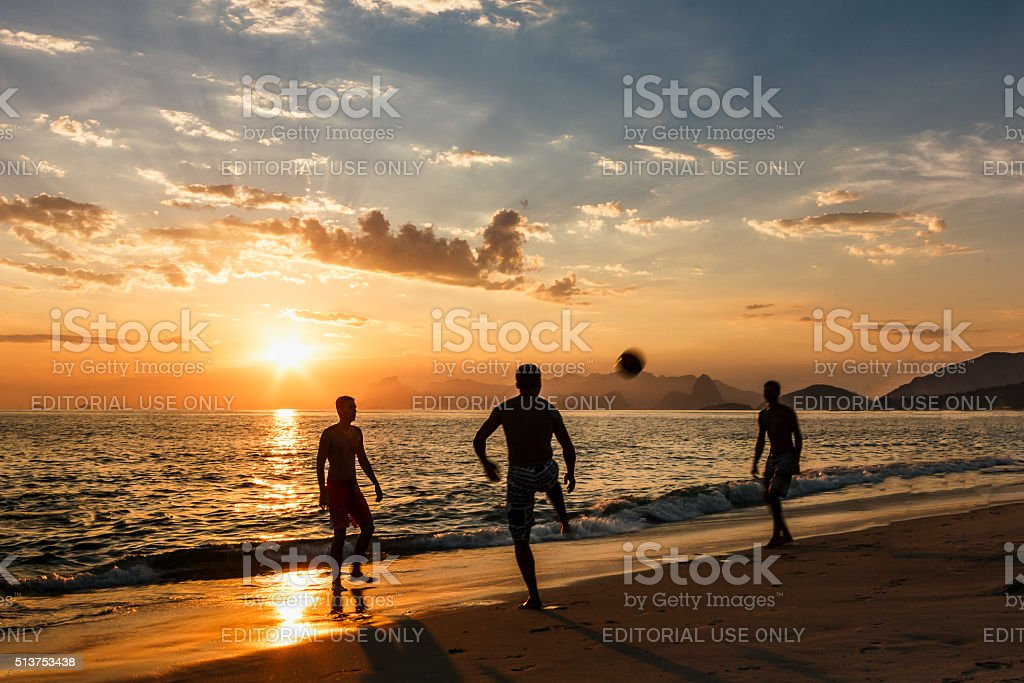 Friends Playing Footbal on a Beach by Sunset stock photo