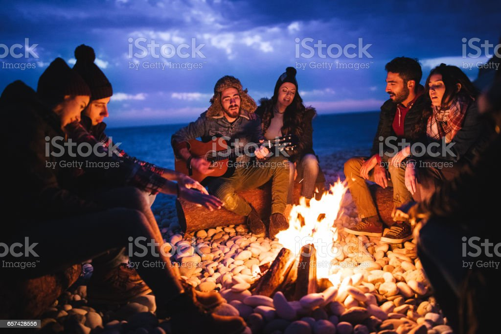 Friends playing guitar and singing around bonfire at the beach stock photo