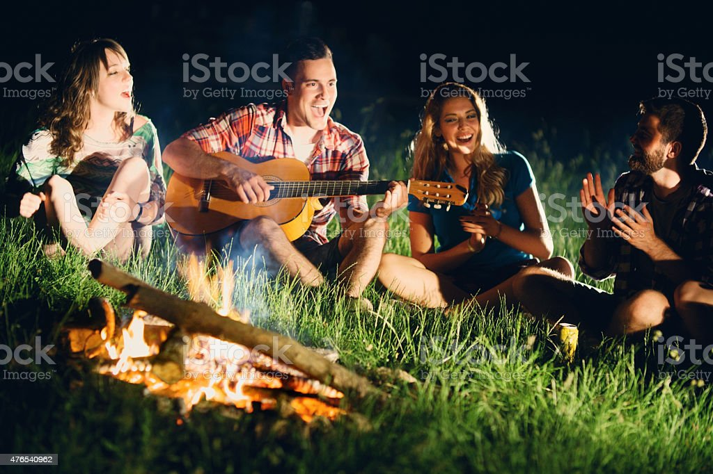 Friends playing guitar gathered around campfire. stock photo