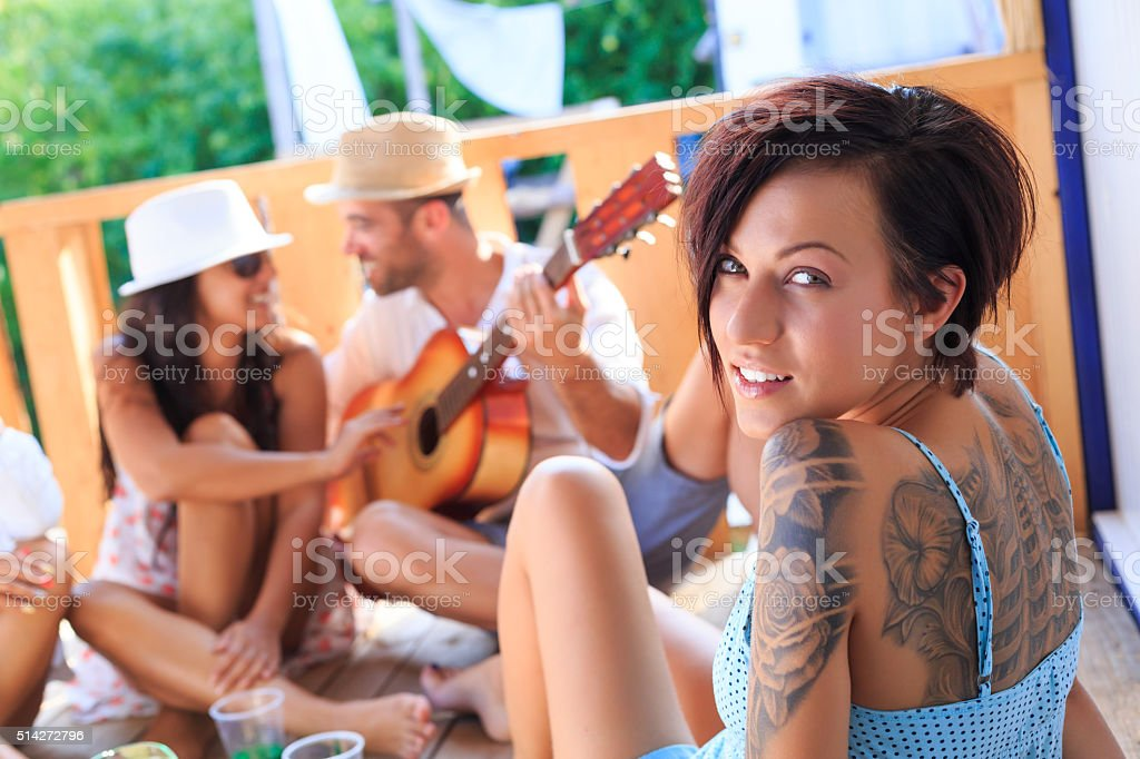Friends playing guitar on pavilion stock photo