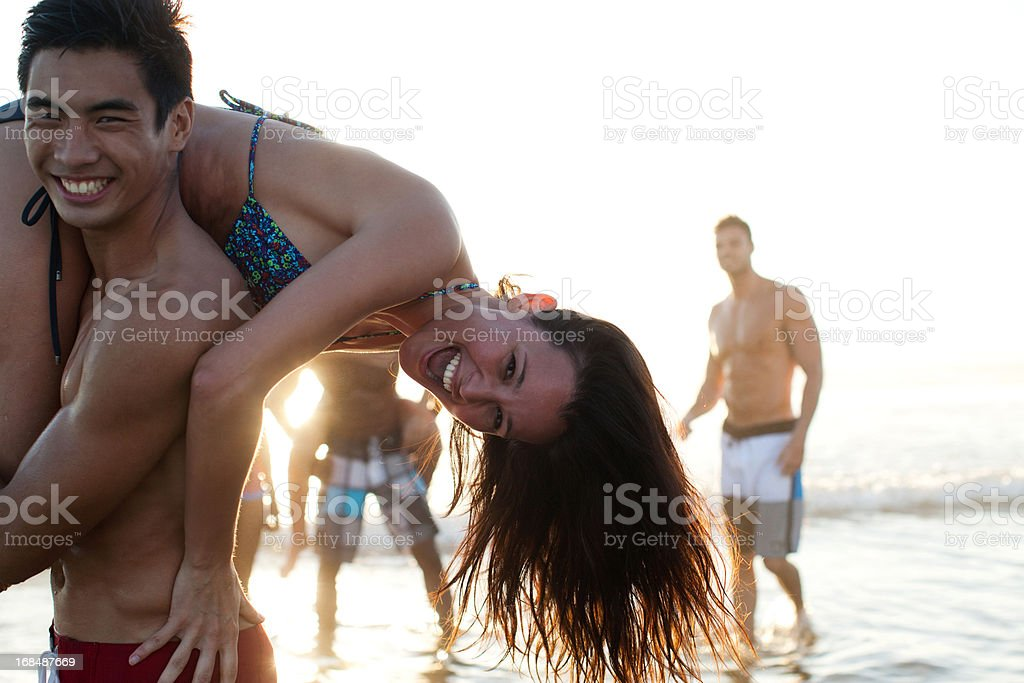 Friends playing in waves on beach royalty-free stock photo