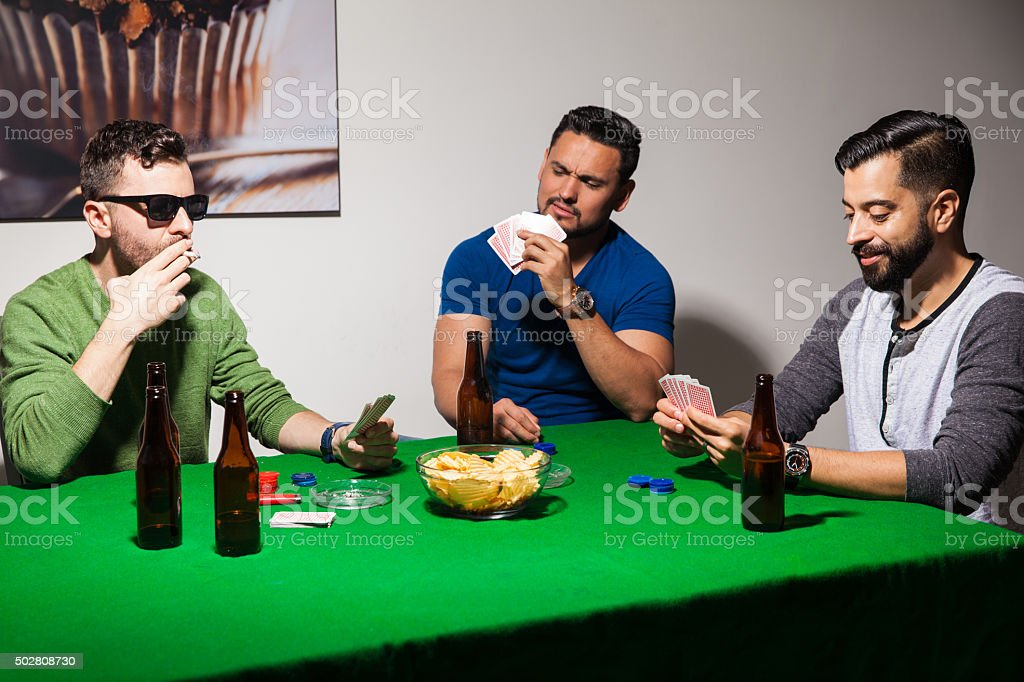 Friends playing poker at home stock photo