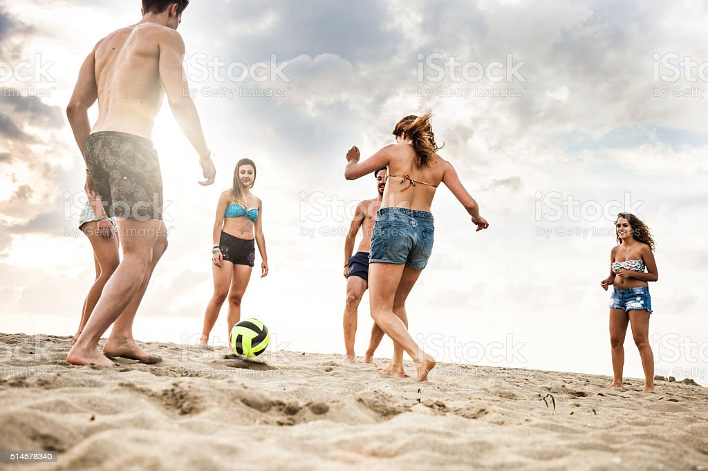 Friends playing soccer during vacations on the beach stock photo