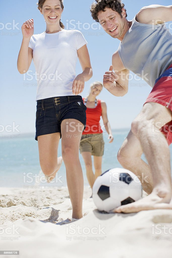 Friends playing soccer on beach stock photo
