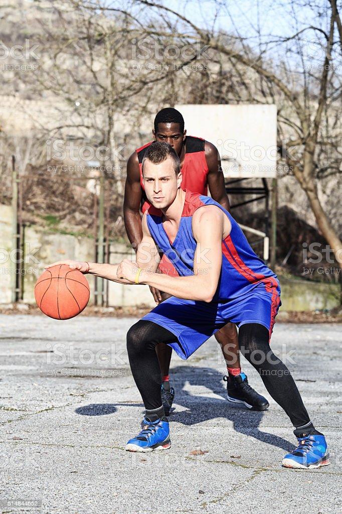 Friends playing street basketball-dribbling stock photo