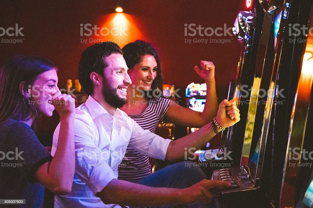 Friends Playing The Slots stock photo
