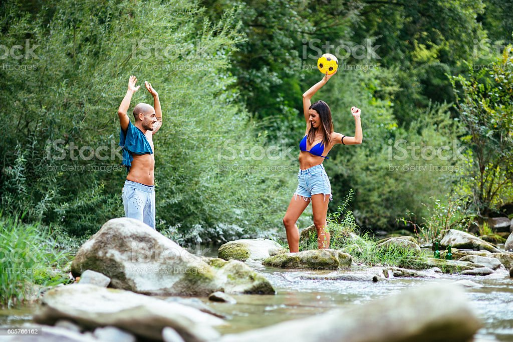 friends playing volleyball on the river stock photo