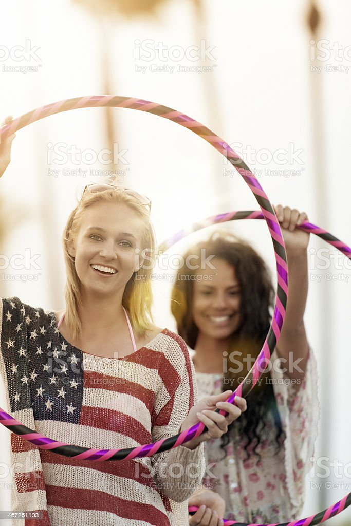 Friends playing with hula hoop stock photo