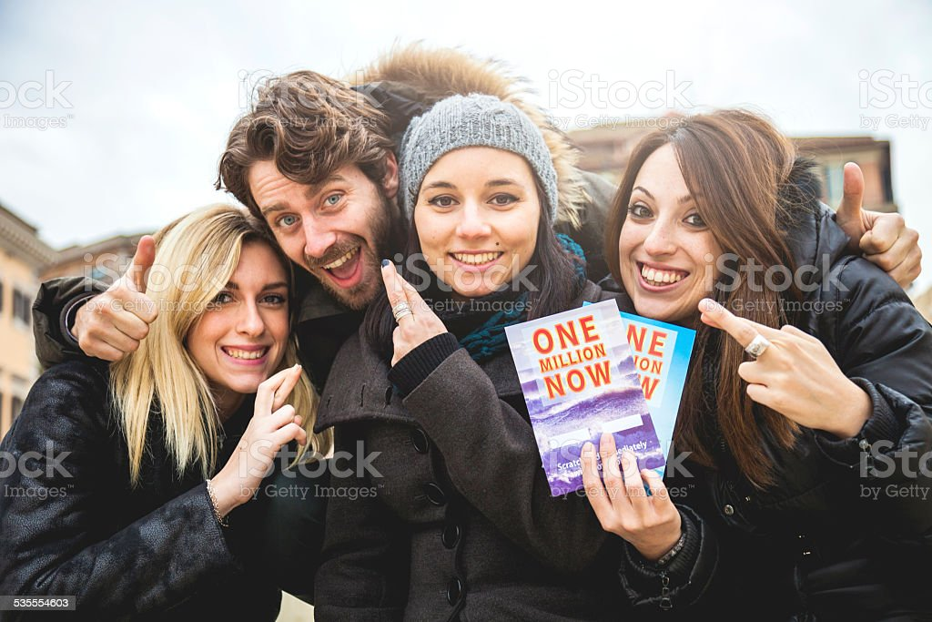 Friends playing with Lottery scratch game ticket stock photo