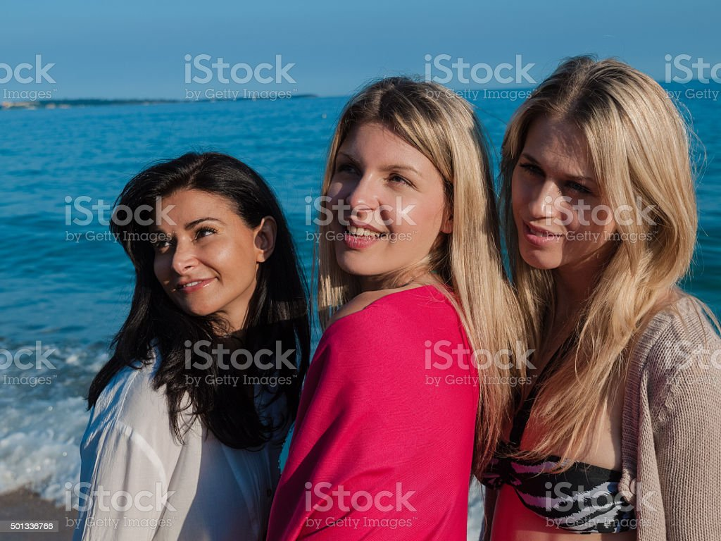 Friends posing for a photo in the beach stock photo