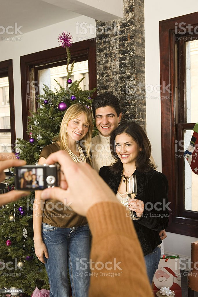 friends posing for camera at christmas party celebration royalty-free stock photo