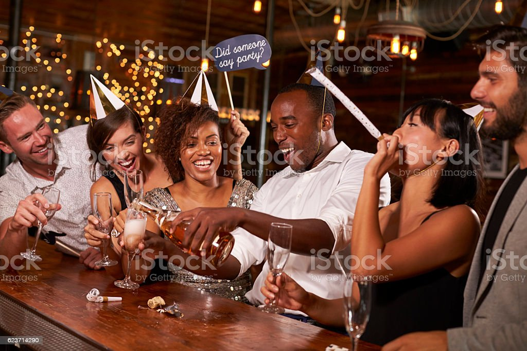 Friends pouring champagne at a New Year's party at a bar stock photo