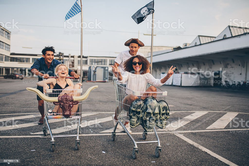 Friends racing with shopping cart stock photo