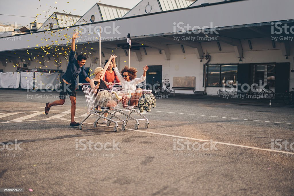Friends racing with shopping carts on road stock photo