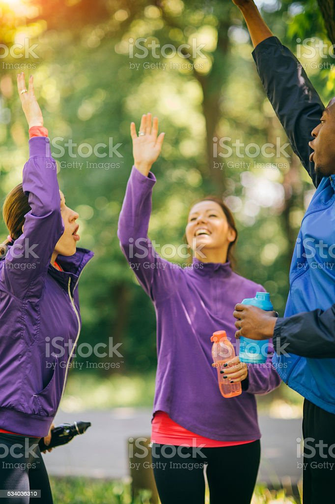 Friends Raising Hands After Jogging. stock photo