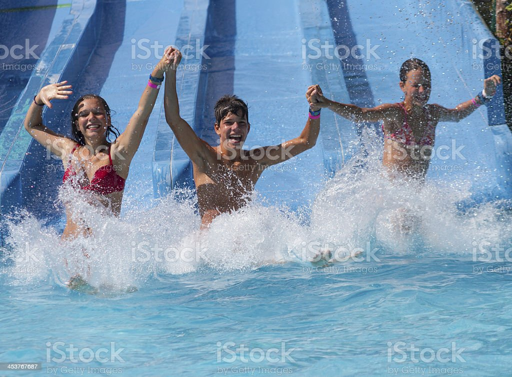 Friends reach the bottom of the slide together stock photo