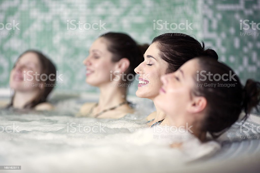 friends relaxing in jacuzzi at health spa stock photo