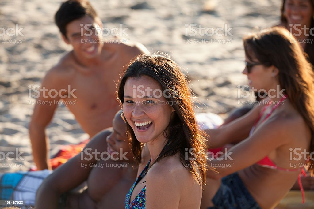 Friends relaxing on beach blanket together royalty-free stock photo