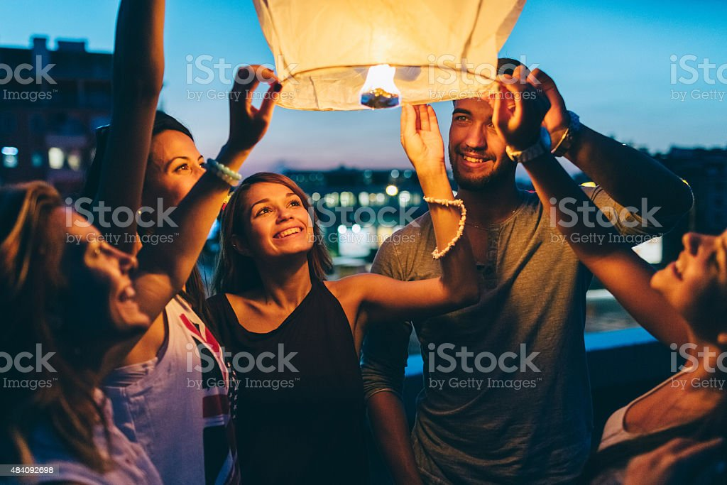 Friends releasing paper lantern for New Year stock photo