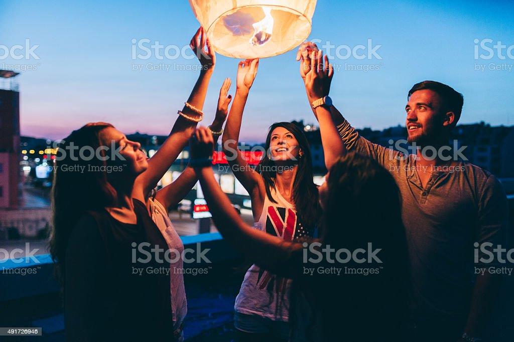 Friends releasing paper lantern stock photo