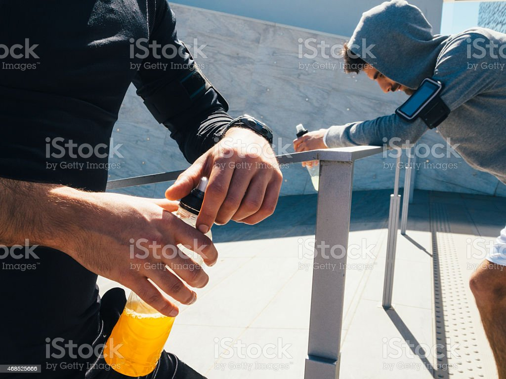 Friends Resting And Drinking An Energy Drink While Training stock photo
