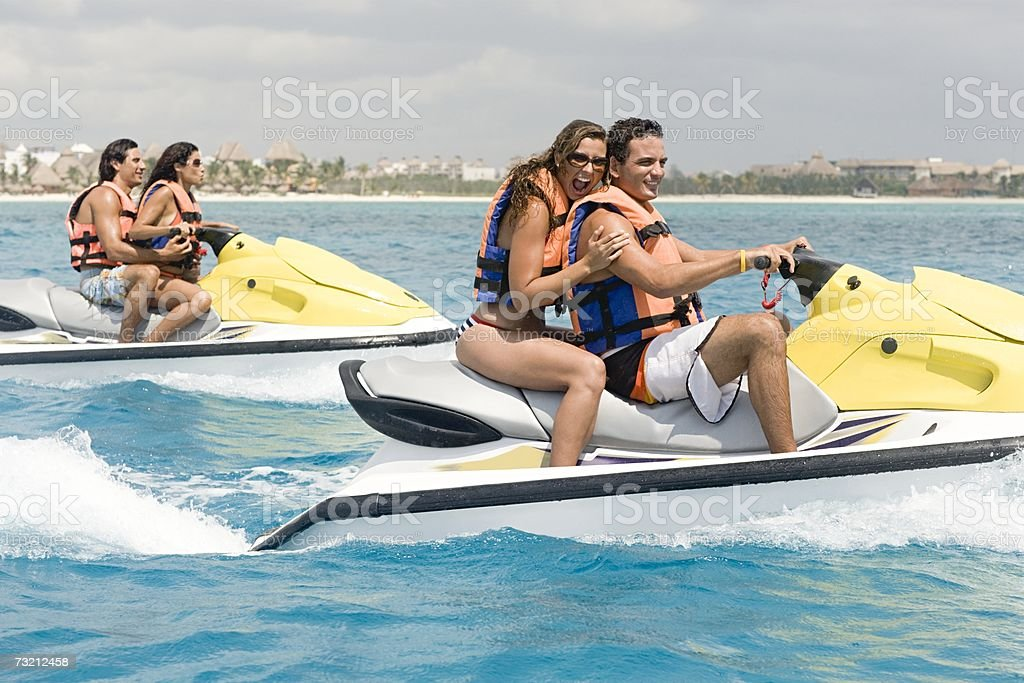 Friends riding jet skis stock photo