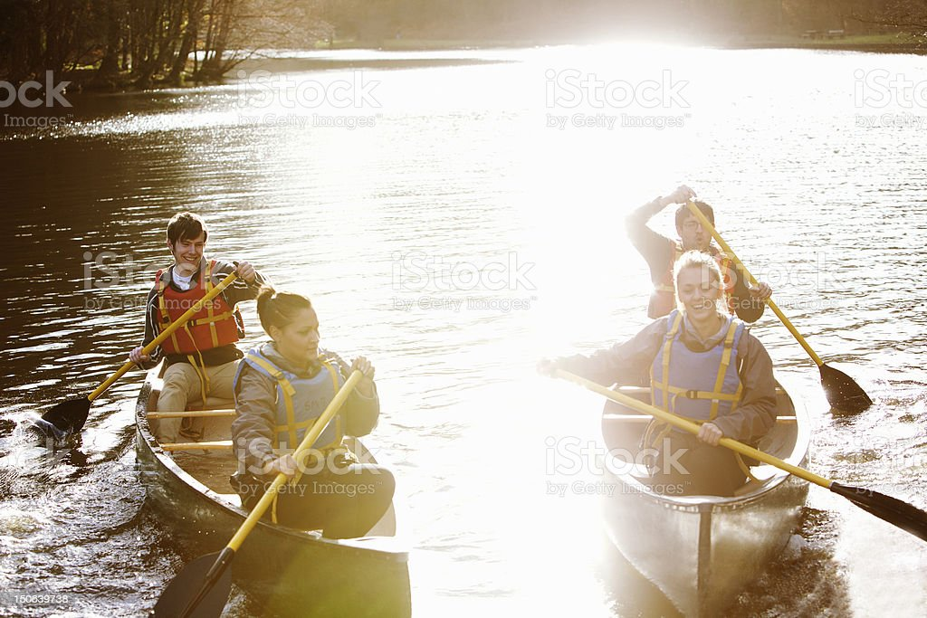 Friends rowing canoes on still lake stock photo