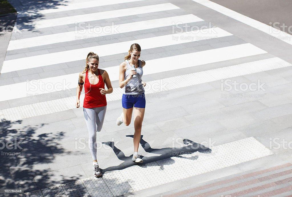 Friends running across urban crosswalk royalty-free stock photo
