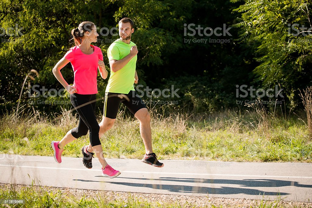 Friends running and talking together stock photo