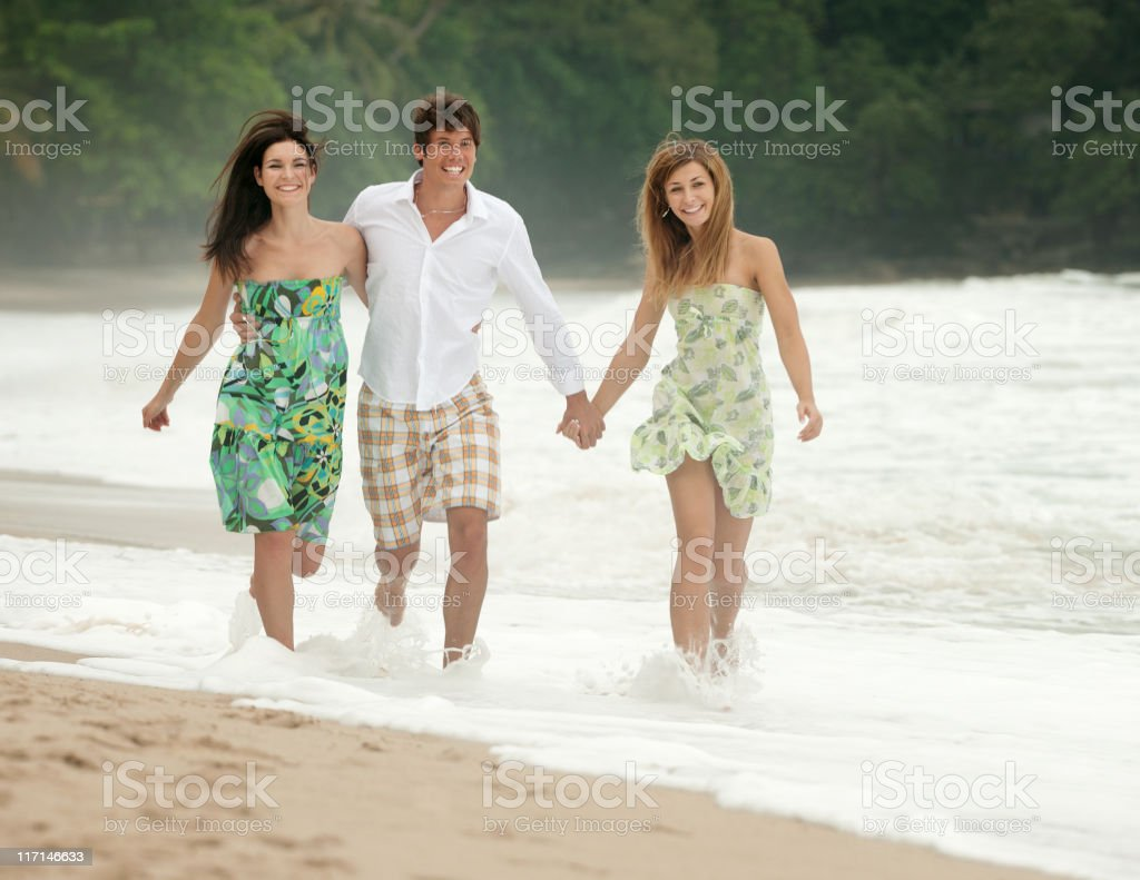 Friends running down Paradise Beach royalty-free stock photo