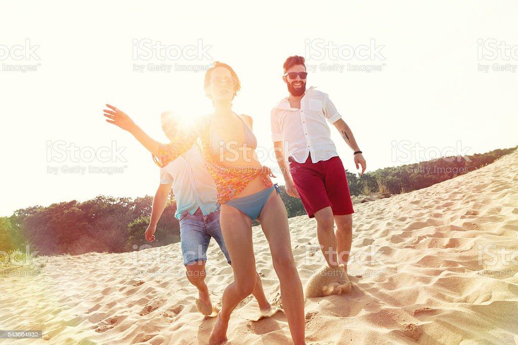 Friends running down the beach stock photo