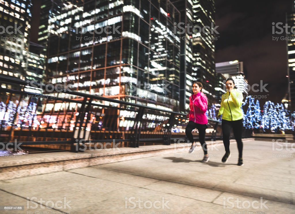 friends running in london in canary wharf stock photo