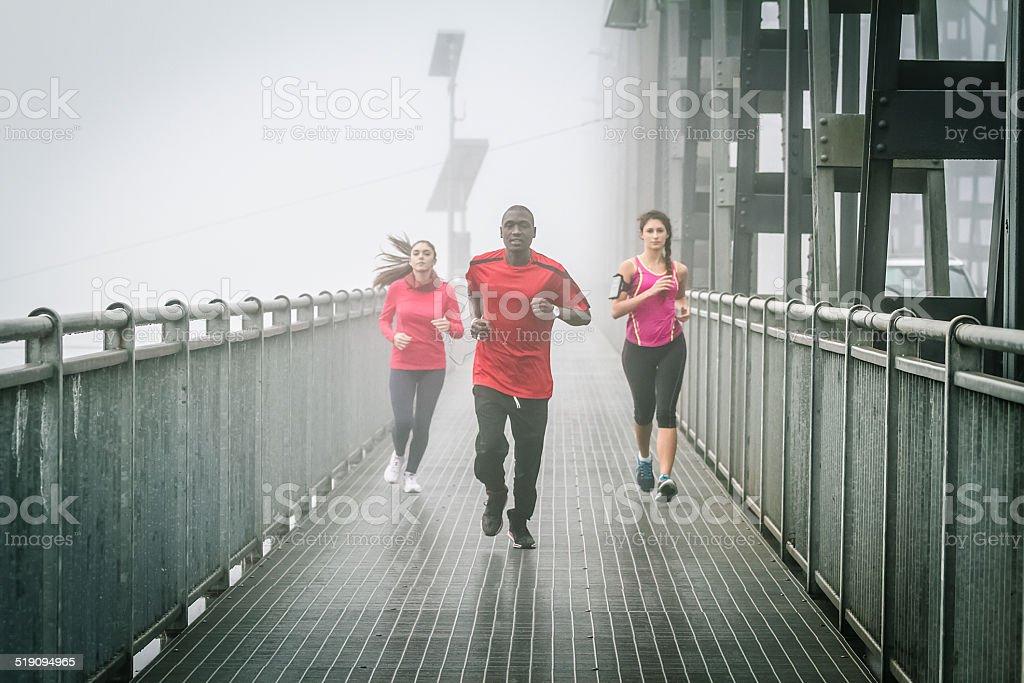 Friends Running in the fog on Iron Bridge stock photo