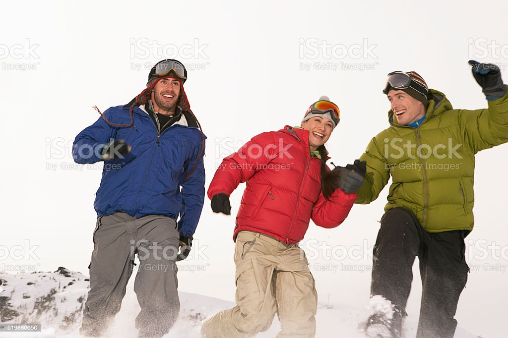 Friends running in the snow stock photo