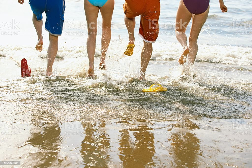 Friends running in the surf stock photo