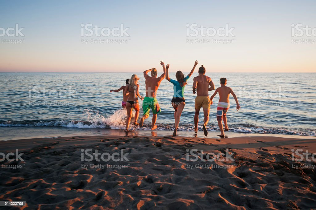 Friends running in to sea stock photo