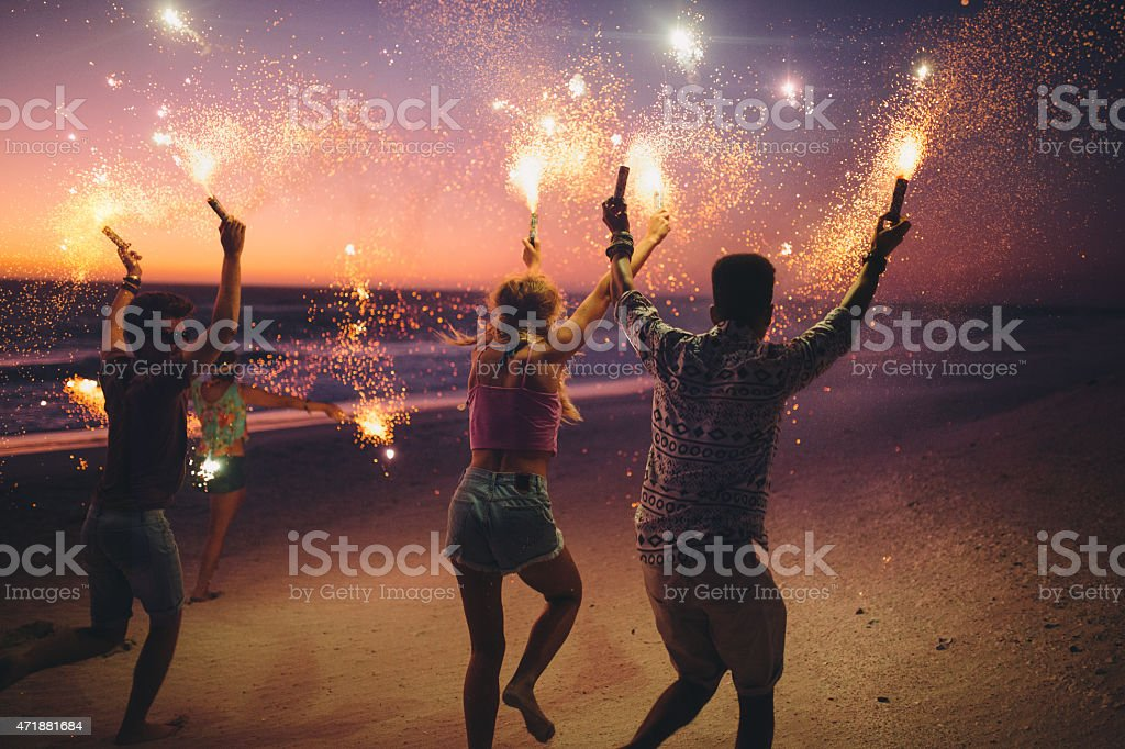 Friends running on a beach with fireworks stock photo