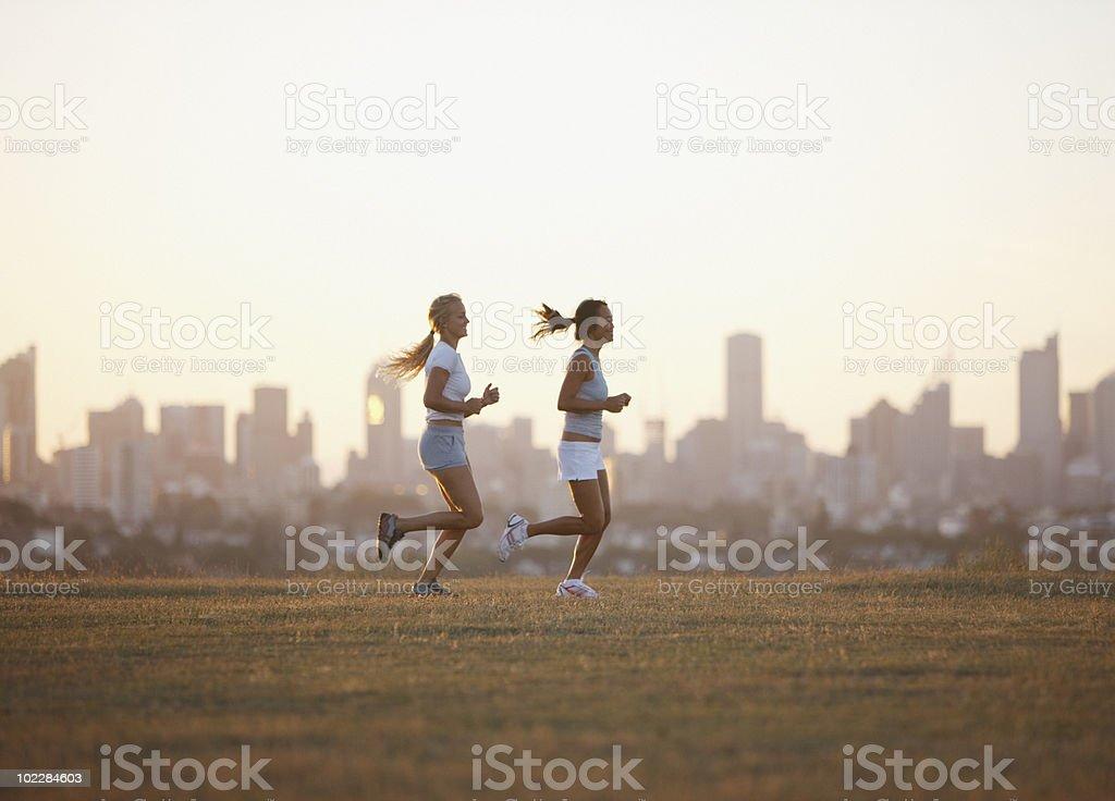Friends running through field stock photo