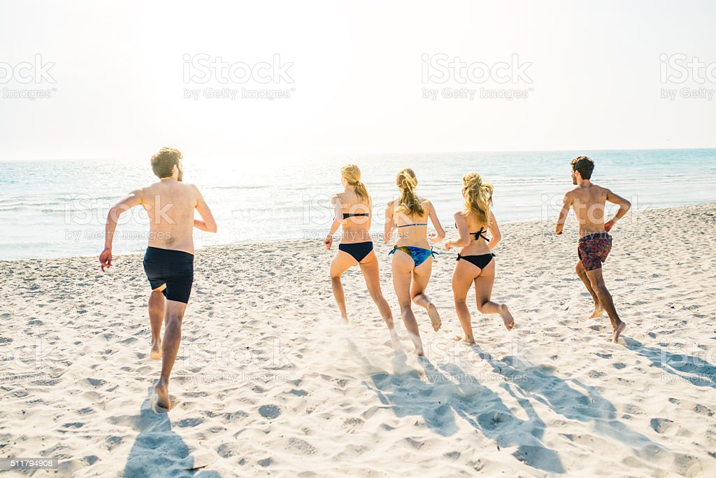 Friends Running To The Sea stock photo