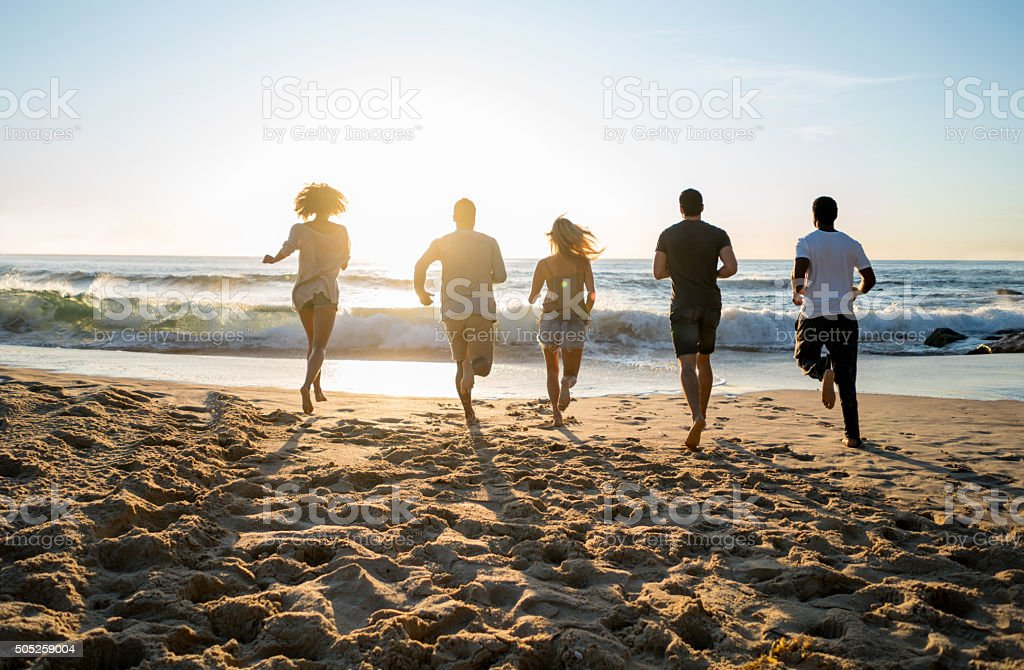 Friends running towards the sea at the beach stock photo