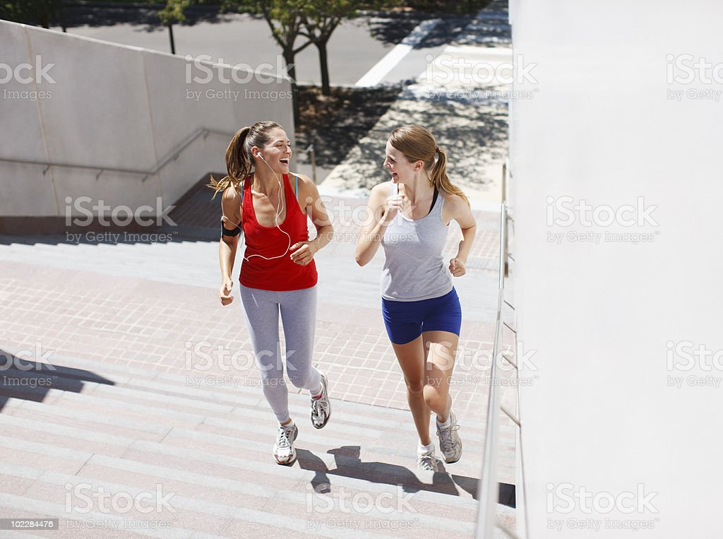 Friends running up urban staircase royalty-free stock photo