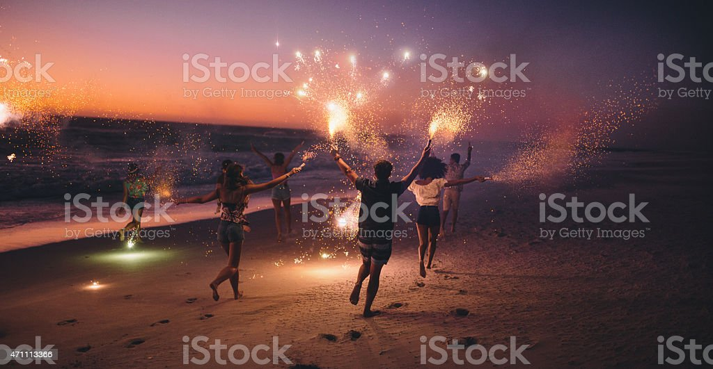 Friends running with fireworks on a beach after sunset stock photo