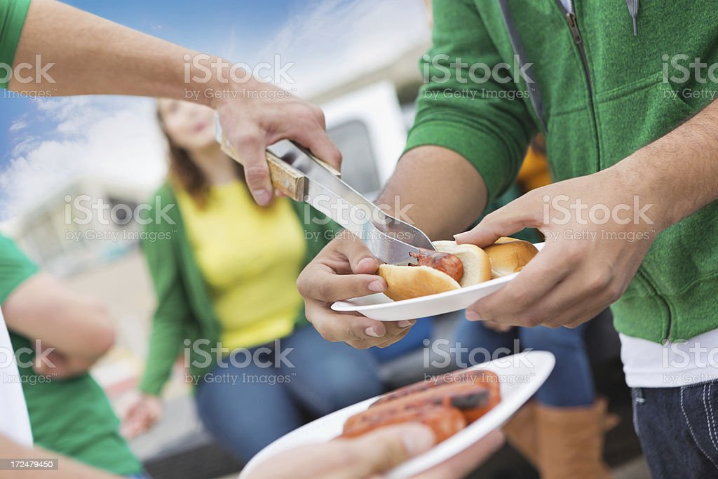 Friends serving hot dogs and cooking out at tailgate party stock photo