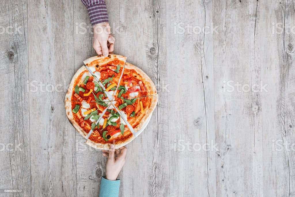 Friends sharing a pizza royalty-free stock photo