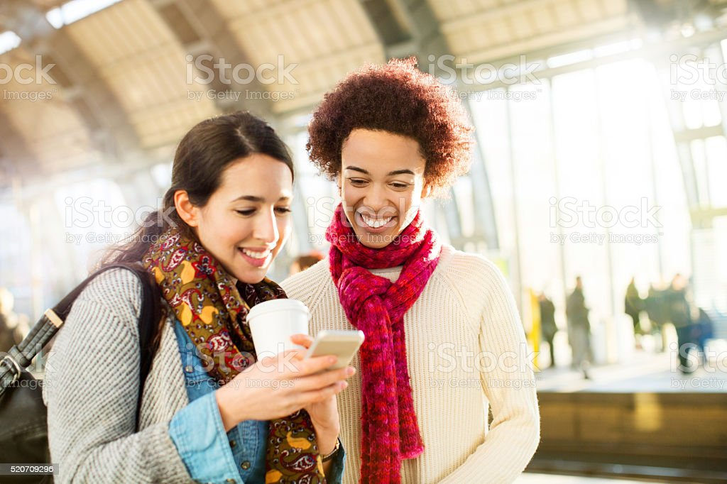 Friends sharing messages on their smartphone stock photo