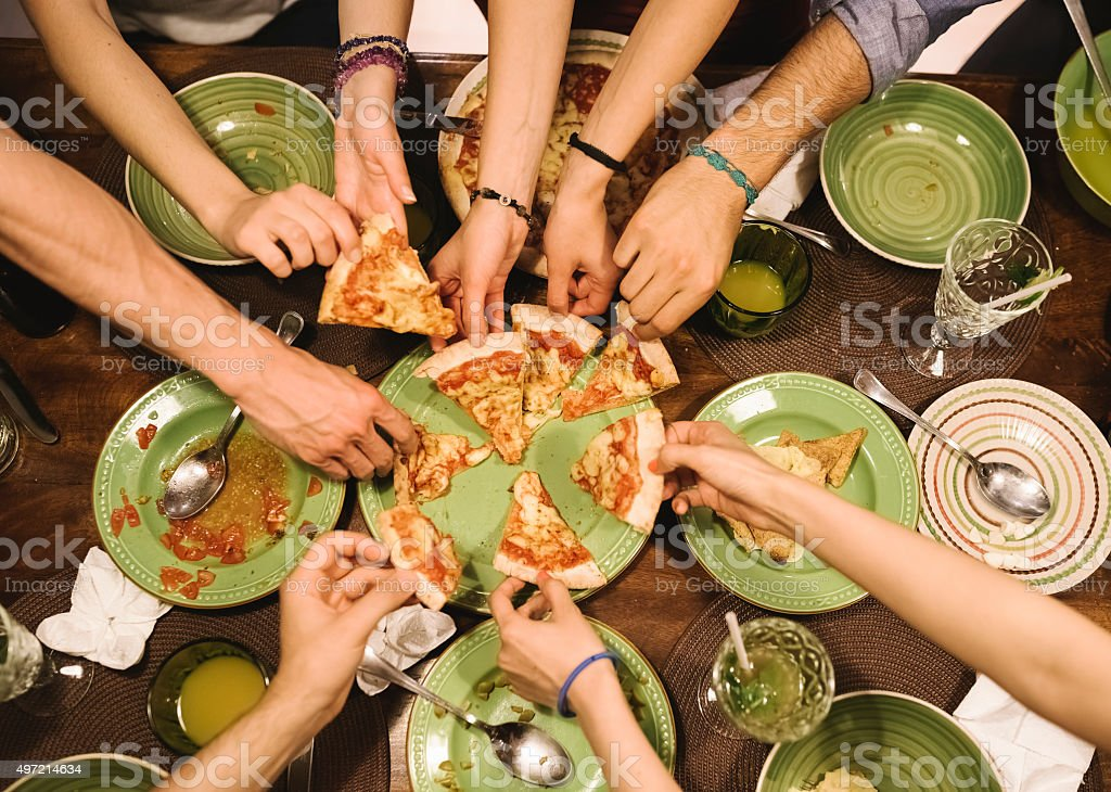 Friends sharing pizza at home stock photo