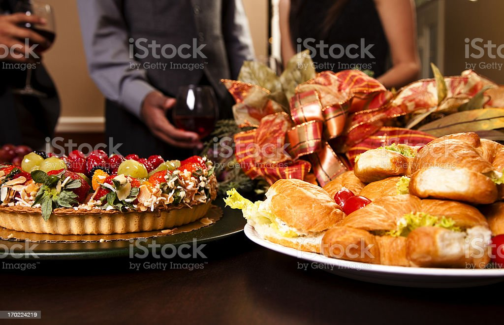 Friends sharing wine, food, appetizers. Holiday dining. stock photo
