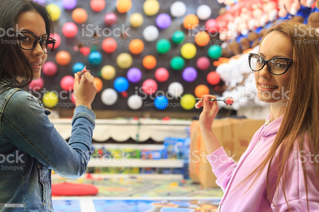 Friends shooting with darts on multicolored ballon stock photo