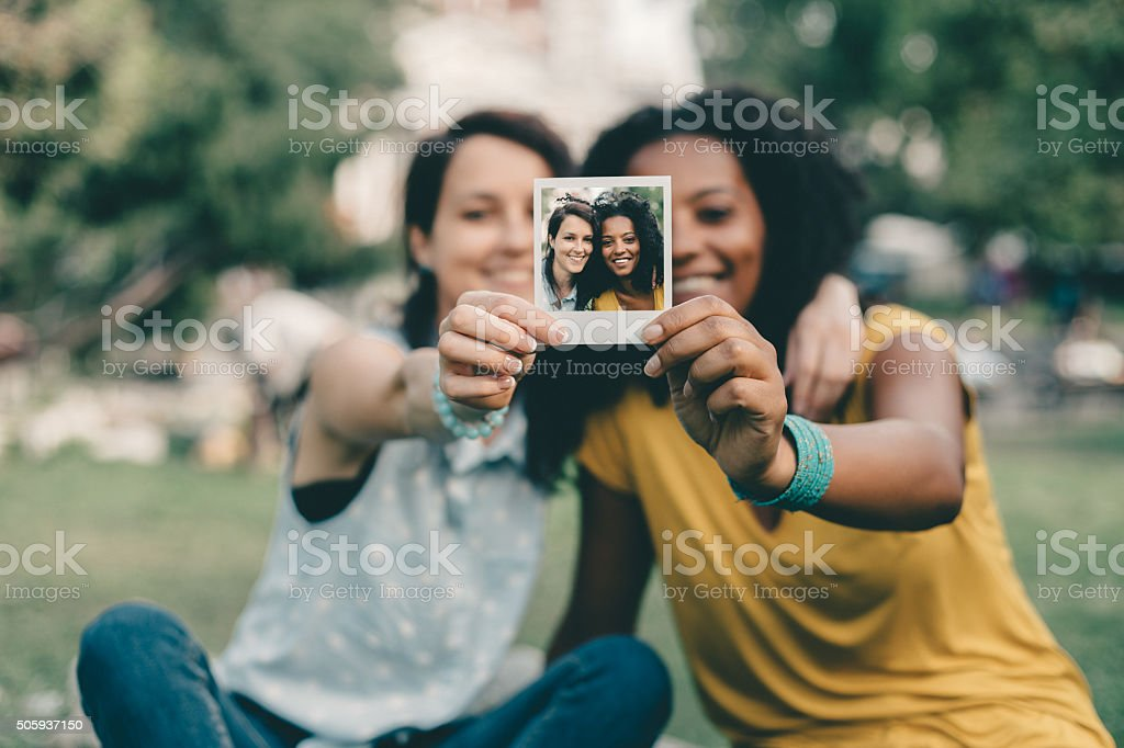 Friends showing instant photo stock photo